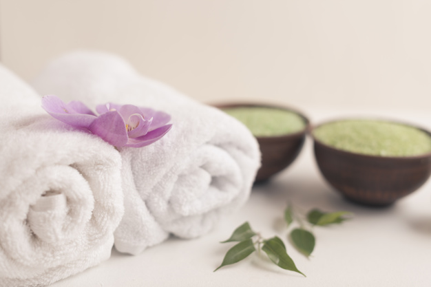 orchid-on-rolled-up-towel-with-spa-salt-on-white-background_23-2147867864